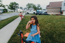 Girl Sitting On A Dirt Bike Eating An Apple.