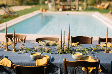 Table With Linen Tablecloth And Bouquets Located Near Pool During Wedding