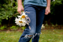 Boy Stands Holding Bouquet Of Daisies