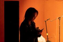 A Female Rock Singer Is Using Her Mobile Phone Backstage