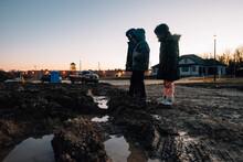 Children Standing At Dusk In Construction Zone.