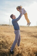 Happy Man Tossing Daughter In Rural Meadow