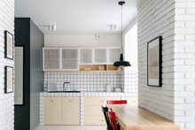 Kitchen Area In A Minimalist Apartment With Colourful Chairs And White Brick Wall