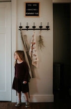 Young Caucasian Girl Standing In Kitchen At Home With Inspirational Quote On The Wall.