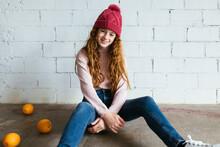 Girl In Warm Clothes Sitting Near Brick Wall