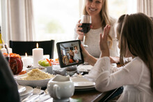Thanksgiving: Girl Waves To Relative On Tablet Video Chat
