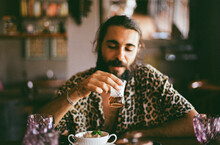 Man In A Leopard Shirt At The Dinner Table Drinks Tea