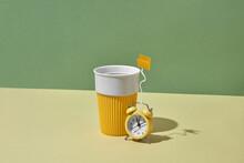 Alarm Clock As A Teabag Near Ceramic Reusable Cup.