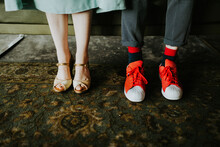 Close Up Of Bride Wearing Golden High Heels And Groom Wearing Bright Red Sneakers