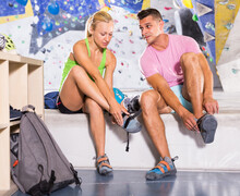 Athletic Man And Woman Equipping For Climbing Workout At Bouldering Gym..