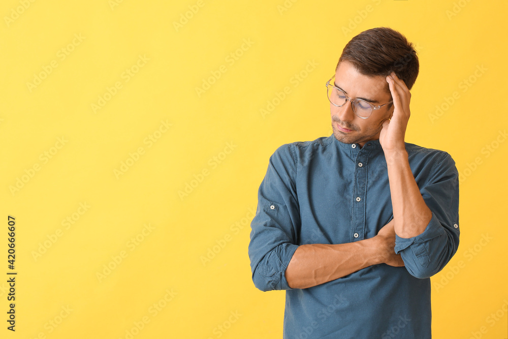 Fototapeta Portrait of thoughtful young man on color background
