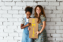 Cheerful Diverse Girls With Poster