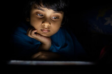 Little Girl Watching And Browsing Movie In A Tablet Inside Room
