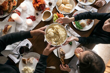 Thanksgiving: Mashed Potatoes Passed Across Table From Overhead