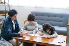 子供たちに勉強を教える父親