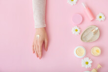 Female Hand With Cosmetic Products And Beautiful Flowers On Color Background