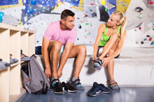 Young Man And Woman Equipping For Climbing Workout At Bouldering Gym