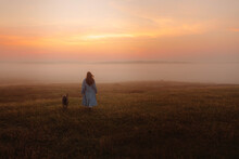 A Girl With A Long Hair Wearing A Long Blue Coat Walking In The Middle Of The Foggy And Misty Field With A Dog By Side N The Early Morning With An Orange Red Sky