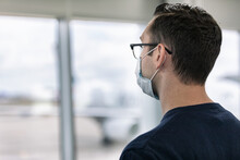 Travel: Anonymous Man Stands Alone Looking Out To Tarmac