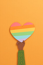 Human Hands Holding Heart With Rainbow Flag As A Symbol Of LGBT Isolated Over Orange Background