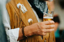 Close Up Of A Cowboy Holding A Glass Of Beer