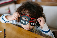 Kid Covering Her Face With A Decorated Cardboard Mask Looking At Camera