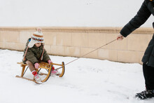 Kid Riding A Sleigh Pulled By An Anonymous Arm