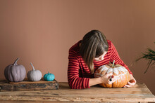 Girl Decorating A Pumpkin