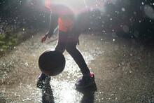 Child Dribbles Basketball In The Rain