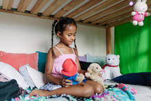 Girl Playing With Stuffed Animals In Her Bedroom