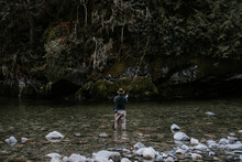 Fly Fisherman Wearing Hip Waders Fishes In A Stream.
