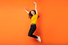 Young Asian Girl Jumping Up On Orange Background