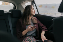 Young Woman Typing A Message On Phone In The Car