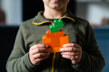 Child With Pumpkin Made Of Colored Block Toys