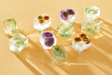Ice Cubes With Flowers On Yellow Background