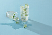 Glass Of Ice Cubes With Flowers On Blue Background