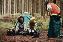 Friends Laughing While Camping In A Forest