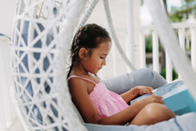 Girl Reading In Hanging Chair