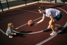 Mother With Little Child Playing Basketball Ball On Sports Ground
