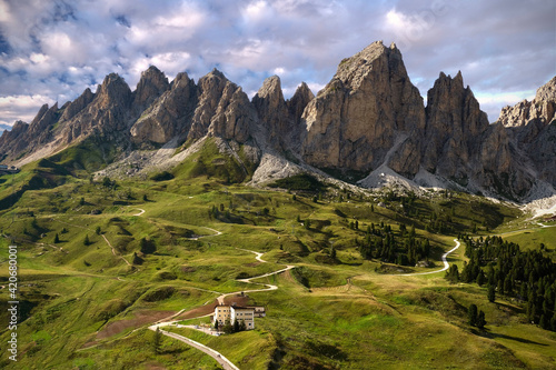 Fototapeta Scenic view of mountain pass. Rocky mountains and green grass meadows. Hotel in Gardena Pass. Dolomites. Italy obraz
