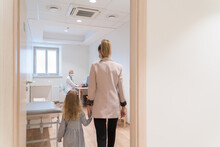 Mother And Daughter Entering In Pediatrist Consulting Room