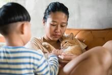 Asian Woman Hugging Orange Cat