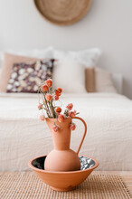 Vase And Bowl With Flowers Near Bed