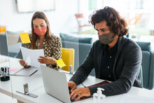 Young Coworkers In Masks Working In Office During Coronavirus Pandemic