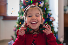 Playful Little Girl In Front Of A Christmas Tree