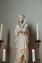 Statue Of Maria With Jesus In Between Candles