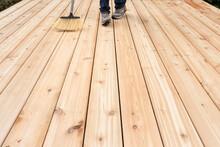 Feet Of Child Sweeping Cedar Deck