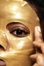 Woman Applying Golden Cosmetic Mask On Face
