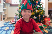 Boy Sitting In Front Of A Christmas Tree