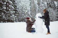 Happy Couple Making A Snowman In Snowy Forest. Winter Love Story.